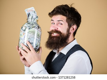 Engaging in investment activity. Happy businessman making a good investment. Bearded man investor smiling with investment money in glass jar. His investment producing income.
