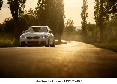 Engels, Russia - June 04, 2018: White car BMW 3 Series F30 is parked on empty countryside asphalt road at sunset