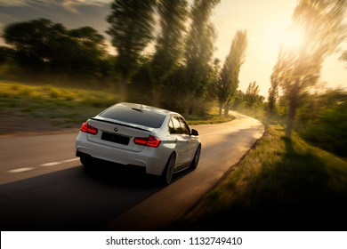 Engels, Russia - June 04, 2018: White car BMW 3 Series F30 is driving on empty countryside asphalt road at sunset