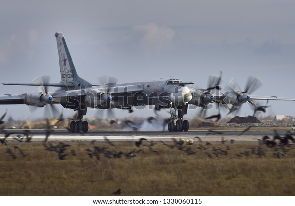 Engels, Saratov Region, Russia - November 08,2012: Routine busy day at the airbase. Flying of Tu-95 (is a large, four-engine turboprop-powered strategic bomber and missile platform) over birds
