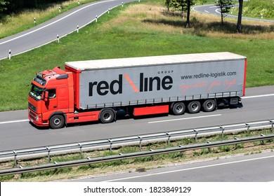 ENGELSKIRCHEN, GERMANY - JUNE 24, 2020: Redline Volvo truck with curtainside trailer on motorway.