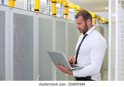 it engeneer businessman with thin modern aluminium laptop in network server room
