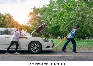 Engine break down.In a young woman pushing a car while the man is Pull the car