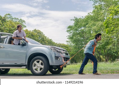 Engine break down.Strong young man pushing a car while woman is emboldening her.Transportation, teamwork, funny concept