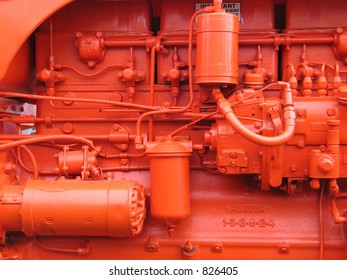 The engine of a brightly painted restored diesel tractor at a country fair.  What a color!