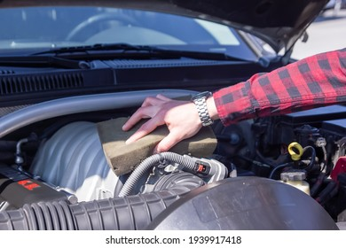 engine of a car, car mechanic cleaning engine