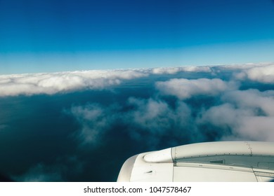 Engine of a commercial jet airplane cruising mid air amongst the vast cloudscape.