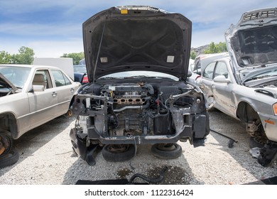 The engine compartment of a wrecked car reveals missing parts, inlcuding the bumper, the radiator and part of the engine