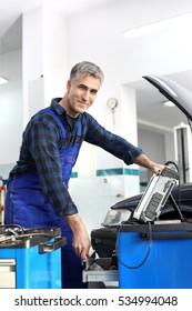 Engine diagnostics. Car in diagnostic station, mechanic connected device