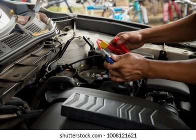 Engine engineer is replacing car battery because car battery is depleted. concept car maintenance.Selective focus charging car with electricity trough cables