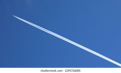 Engine exhaust contrails forming behind an aircraft in the blue sky