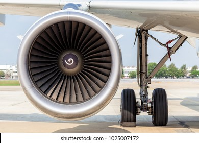 Engine and main landing gear when aircraft park on apron in the airport.
