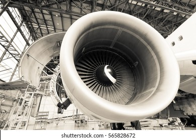 Engine of modern passenger jet plane. Front view. Aircraft air intake and fan blades close up. Engine maintenance and repair. Monochrome in Cream Tone.