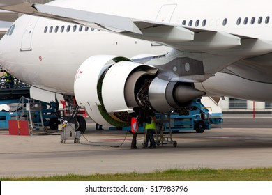 Engine of passenger jet aircraft with open hoods closeup. Engineers and technicians repair the engine of airplane.