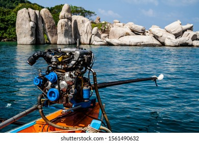 An engine of a Thai Long tail boat, with some boulders in the background.