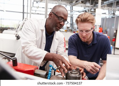 Engineer advising a male apprentice in a factory, close up