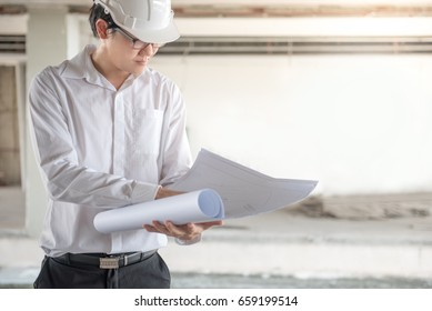 Engineer or Architect checking architectural drawing while wearing a personal protective equipment safety helmet at construction site. Engineering, Architecture and building construction concepts