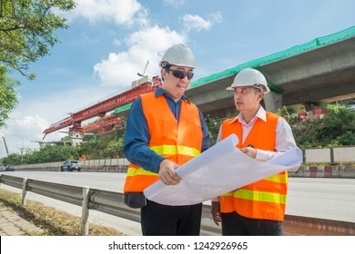 Engineer and Architect or Foreman wear white hardhat and Glow safety cloth meeting in construction site and control Highway Project Development as heavy industrial concept.