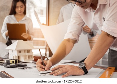Engineer or architect hand sketch the drawing construction building on the desk. Civil engineering, Architect concept.