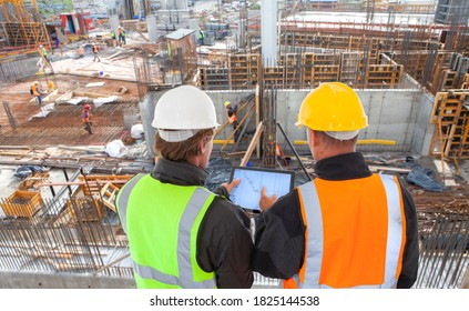engineer architect with hard hat and safety vest working together in team on major construction site on computer tablet