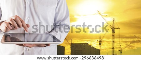 Engineer and architect hold digital tablet computer on sunset sky with clouds and sun background No face Unrecognizable person New highrise apartment buildings and construction cranes Silhouette Crane