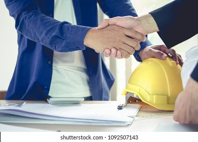 Engineer and architect shake hands agree deal of big lot sales that finish goal of construction plans of the company