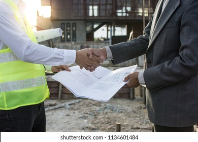 Engineer and Architect shaking hands after finishing  meeting at Construction Site