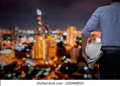 engineer or architect standing and holding helmet and blueprint on night city