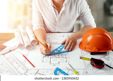 Engineer architect for a stolos with architectural construction drawings. The architect is working on the drawings. The concept of architecture, construction, engineering, design. Copy space.