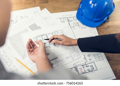 Engineer and architect team discussing floor plan layout for new development in progress on site with blue safety helmet on table