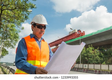 Engineer or Architect wear white Helmet working or reading Construction Plan in Highway or Autobahn Construction site as Industrial or infrastructure Contractor Concept.