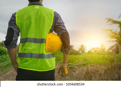 Engineer or architect, wearing green vest, holding yellow safety helmet, water level gauge looking at construction site, empty land with morning sun light Future career, home building construction