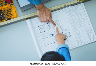 Engineer and architects discussing and pointing to layout building in blueprints on table at factory
