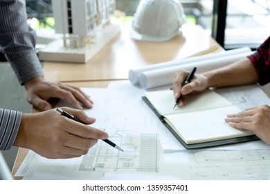 engineer or architectural project, two engineering or architect discussing and working on blueprint with architect equipment, Construction concept.