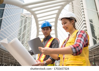 Engineer Asian man and American woman check project plan by company application from digital tablet and paper blueprint. Hapy teamwork at construction site. Win bid auction from internet.