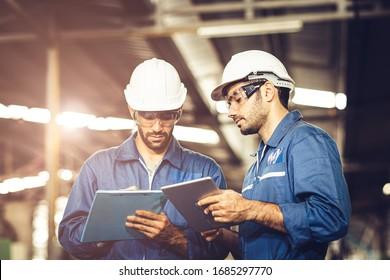 Techniker-Audit-Team zusammen mit Sicherheits-Uniform-und Weißhelm für die Arbeit in der Industrie Handgriff Tablette und Checkliste.