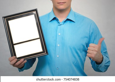 Engineer award mockup. Best worker certificate. Man holding in one hand empty blank photo frame and showing thumbs up gesture sign by another hand. Gratitude concept. Grateful letter.