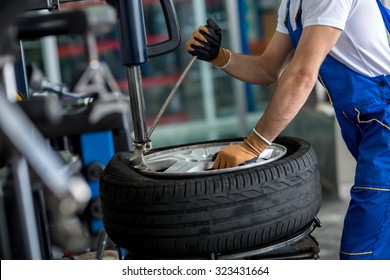 engineer  balancing  car wheel on balancer in workshop