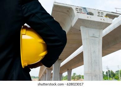 Engineer with bridge under construction background