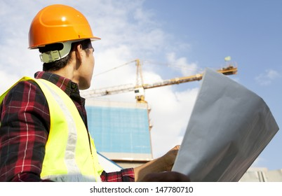 Engineer builder wearing safety vest with blueprint at construction site