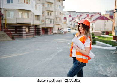 Engineer builder woman in uniform waistcoat and orange protective helmet hold business drawing paper roll against new building. Property living block theme.