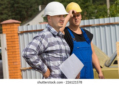 Engineer and building contractor on site standing together in their hard hats watching someone off frame to the right while holding a document