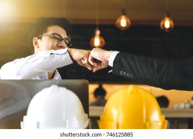 Engineer and businessman handshake,fist collide agreement in negotiations in Business conference finish.Focus on the hands.