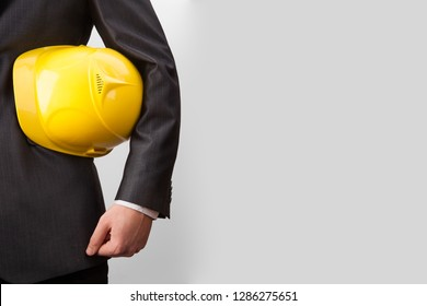 Engineer or businessman holding a yellow helmet under his arm isolated on white, gray background. no face.