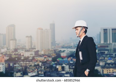 Engineer or businessman wearing a helmet standing alone, looking forward and thinking about building construction and technology building in the city. real estate investment construction concept