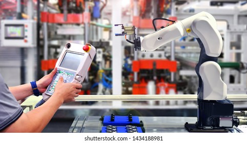 Engineer check and control automation Robot arm machine for Automotive bearings packing process in factory.