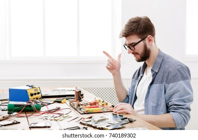 Engineer checking broken motherboard. Computer diagnostic, maintenance support and repairing service concept.