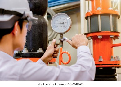 Engineer checking Condenser Water pump and pressure gauge , chiller water pump with pressure gauge.System ready.