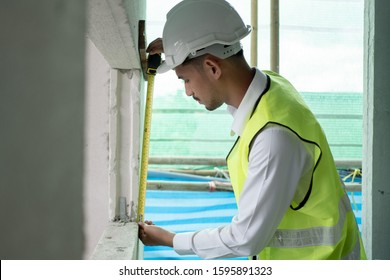 Engineer checking defect in construction site measure dimention of window on wall panel