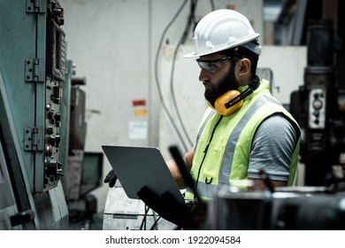 The engineer is checking and inspecting at the factory. He is working with the laptop to check range of votage working.